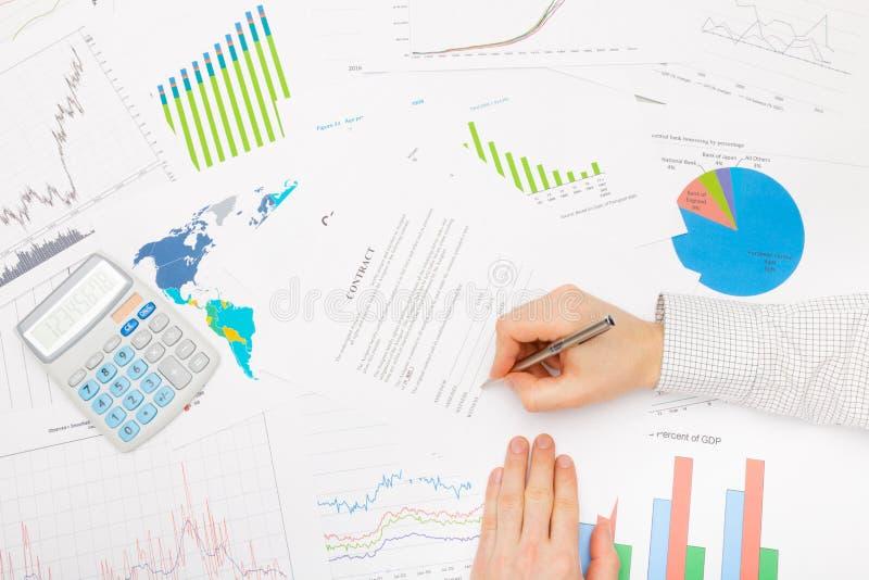 Бизнесмен на таблице с различными финансовыми данными - подписывая контрактом стоковая фотография rf