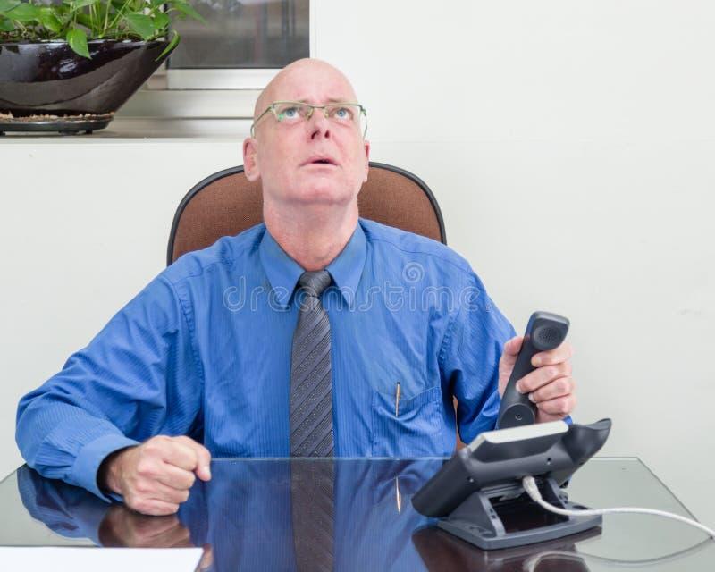 Бизнесмен на телефоне на расстроенном столе, стоковая фотография