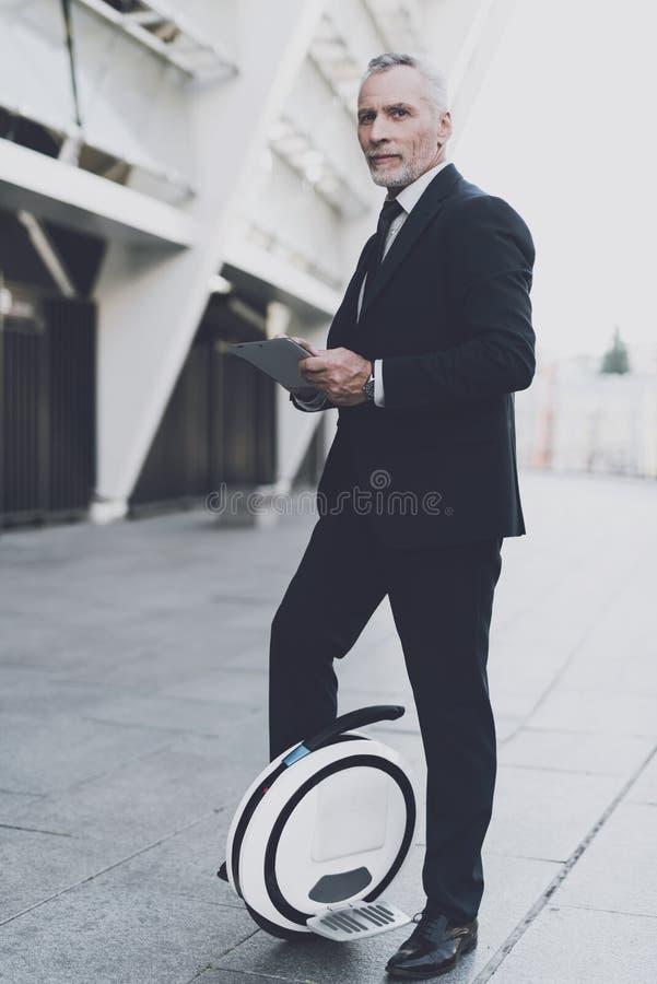 Бизнесмен на monowheel ищет на таблетке стоковые изображения rf