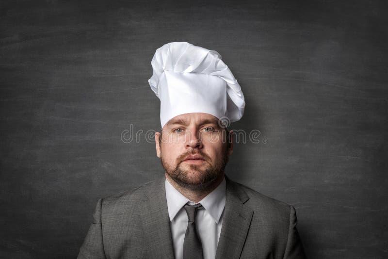 Бизнесмен нося шляпу повара стоковая фотография