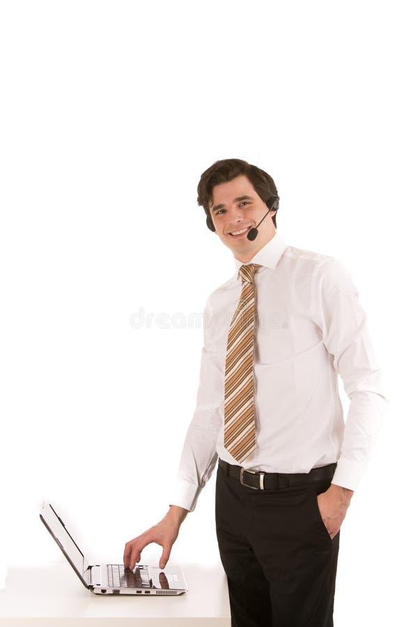 Бизнесмен нося шлемофон на его компьтер-книжке стоковое изображение rf