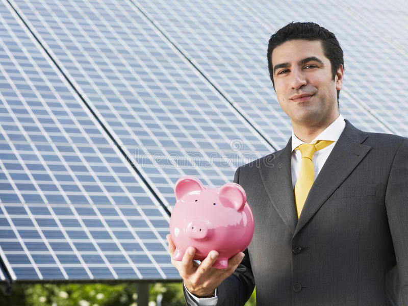 бизнесмен обшивает панелями солнечное стоковое изображение