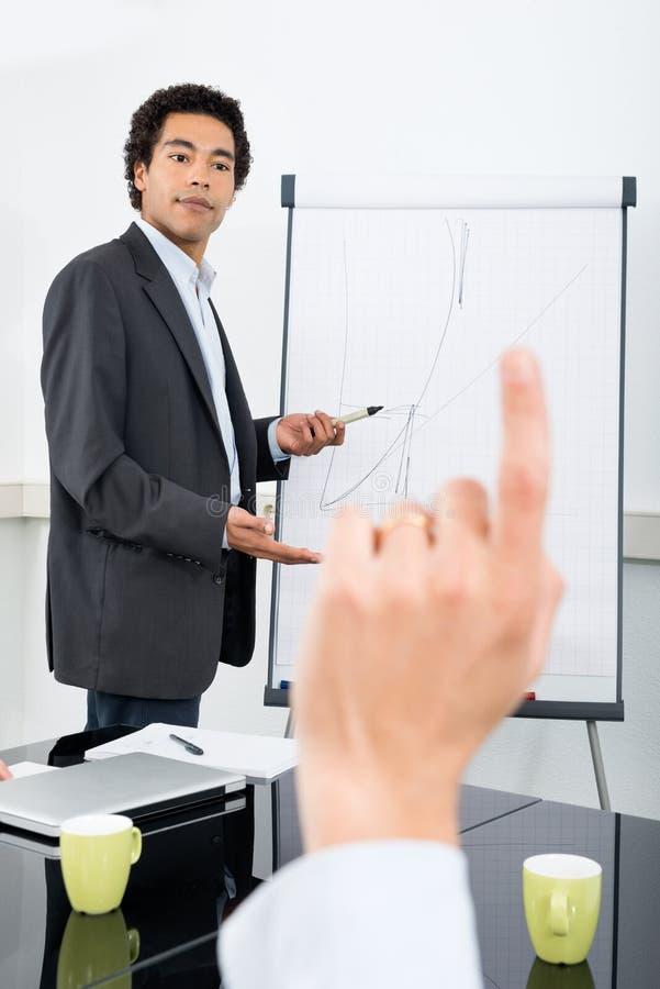 Бизнесмен объясняя диаграмму с рукой повышения коллеги стоковое изображение rf