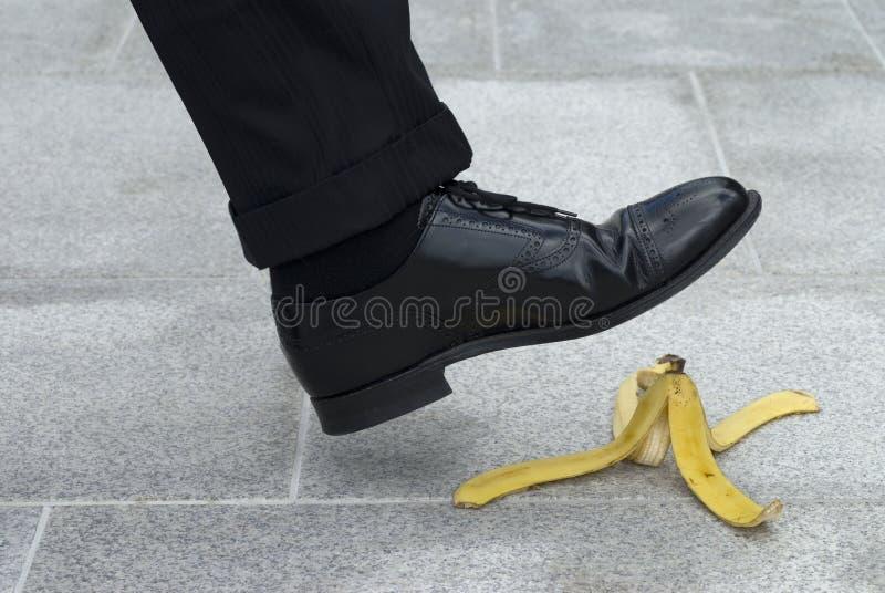 Бизнесмен около к шагу на кожу банана стоковые фотографии rf