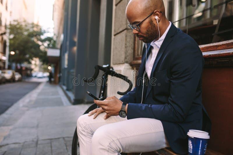 Бизнесмен ослабляя outdoors используя телефон стоковое фото