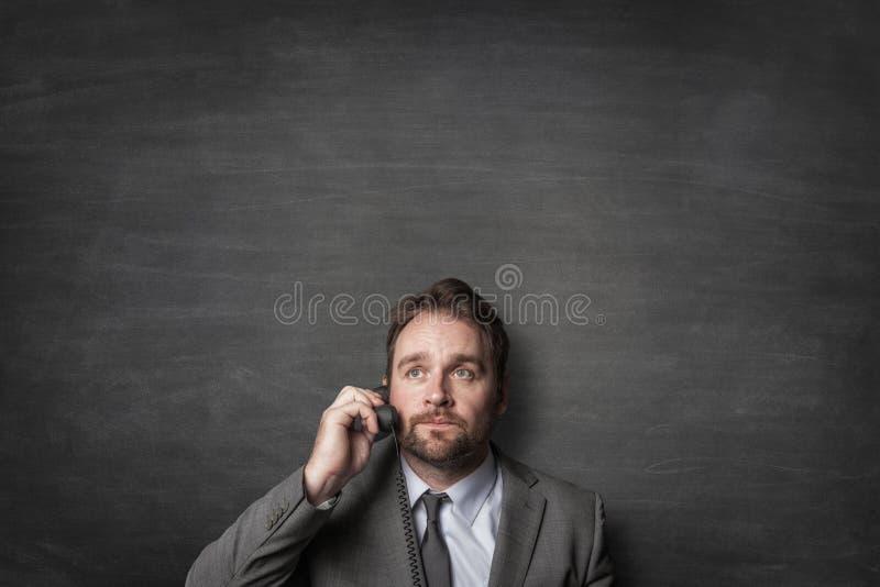 Бизнесмен отвечая по телефону шнура стоковое изображение