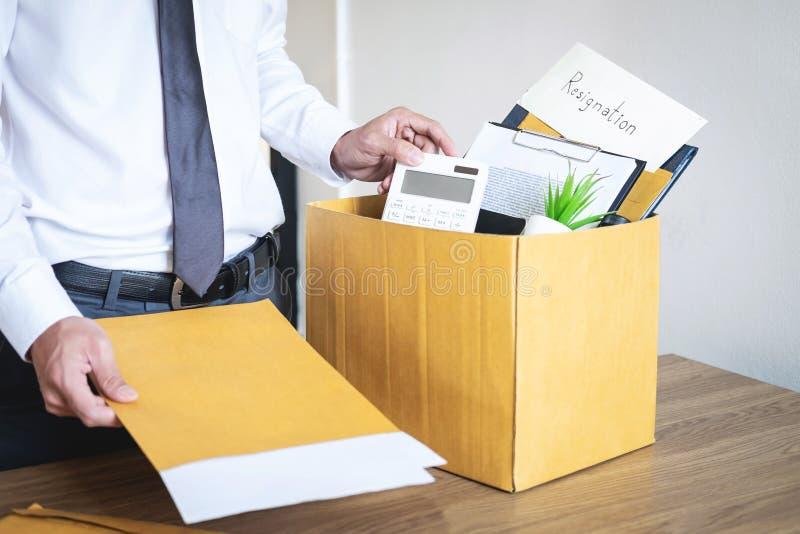 Бизнесмен отправляя письмо будет был безропотностью и пакуя пожитками нося компанией и файлами в коричневую картонную коробку, стоковое изображение