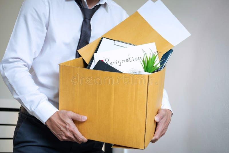 Бизнесмен отправляя письмо будет был безропотностью и пакуя пожитками нося компанией и файлами в коричневую картонную коробку, стоковое изображение rf