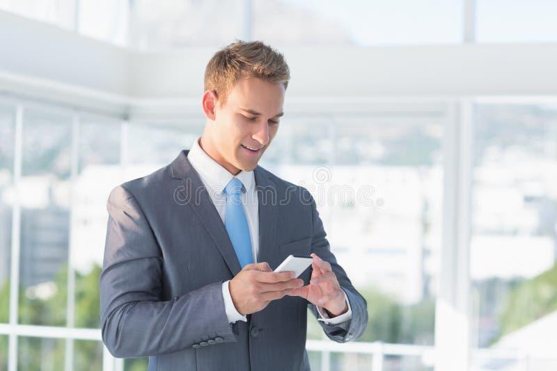 Бизнесмен отправляя СМС с его smartphone стоковая фотография