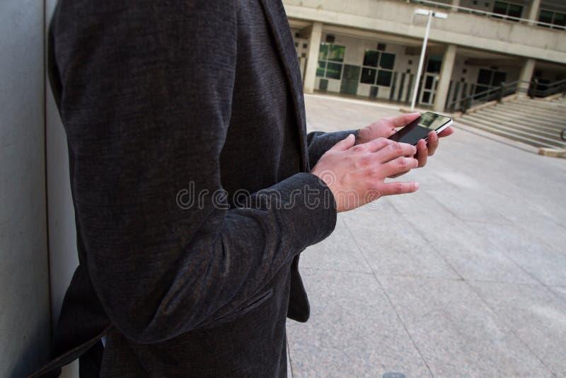 Бизнесмен отдыхая от работы и его разговаривает с его smartphone стоковые фото