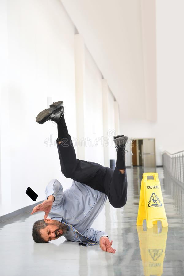 Бизнесмен падая на влажный пол стоковое изображение