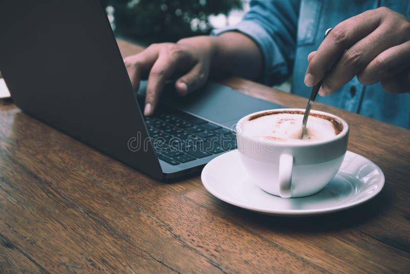 Бизнесмен печатая данные в компьтер-книжку для сводки пока шевелящ кофе стоковое фото