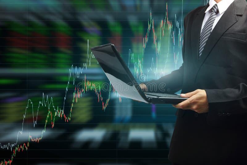 Бизнесмен печатая на современной компьтер-книжке с диаграммой фондовой биржи иллюстрация штока