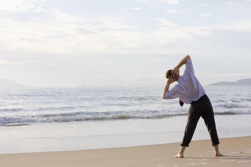 бизнесмен пляжа делая тренировки стоковые фотографии rf