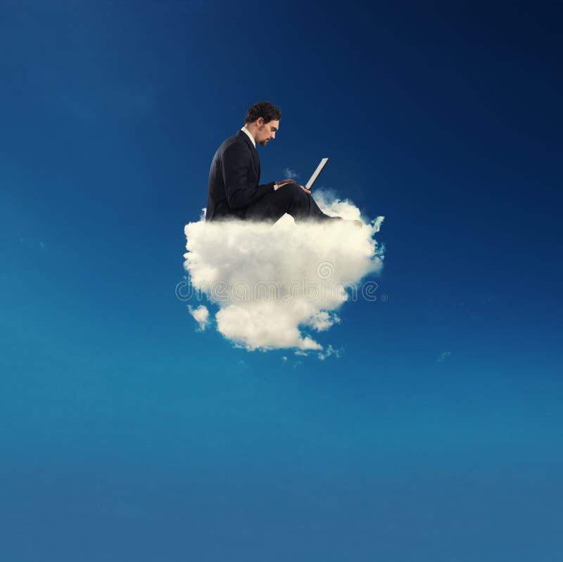 Бизнесмен подключил с его компьтер-книжкой над облаком концепция социальной наркомании сети и интернета стоковые фотографии rf