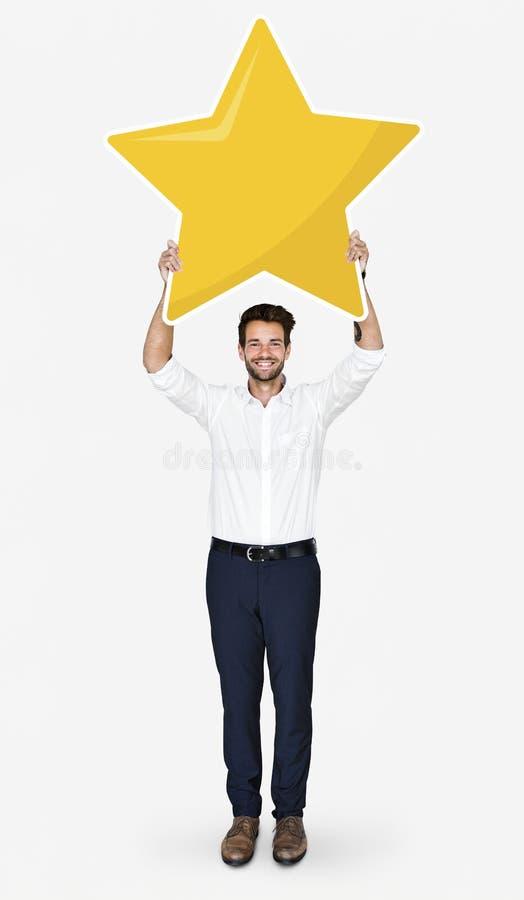 Бизнесмен показывая золотой символ оценки звезды стоковая фотография rf
