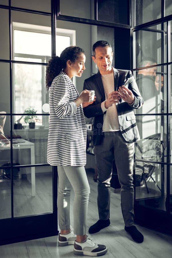 Бизнесмен показывая некоторую электронную почту по телефону к его коллеге стоковое фото