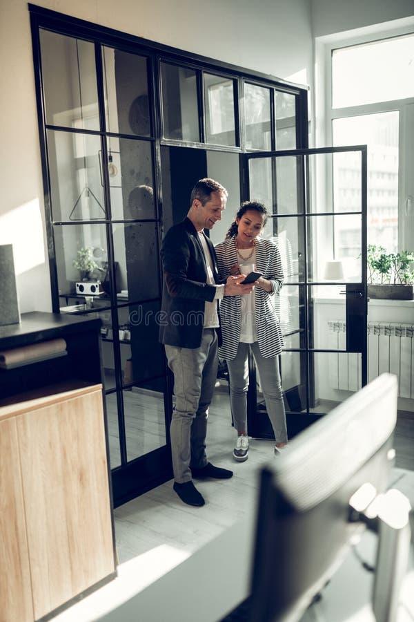 Бизнесмен показывая некоторый вебсайт по телефону к его коллеге стоковое изображение