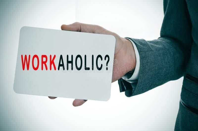 Бизнесмен показывая шильдик с трудоголиком слова стоковое фото