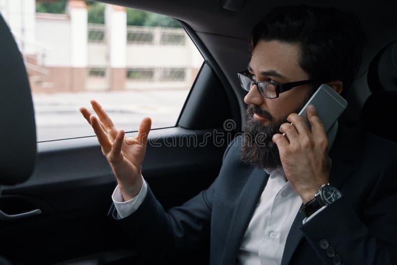 Бизнесмен пока путешествующ автомобилем в заднем сиденье используя sm стоковые изображения rf