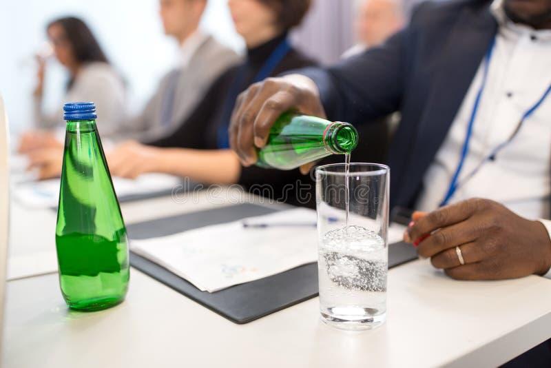 Бизнесмен, поливающий воду в стекло на конференции стоковые изображения rf
