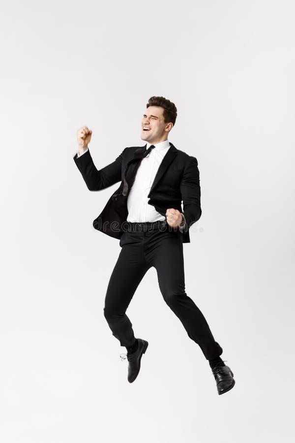 Бизнесмен полнометражного портрета смешной жизнерадостный скача в воздух над серой предпосылкой стоковое изображение rf