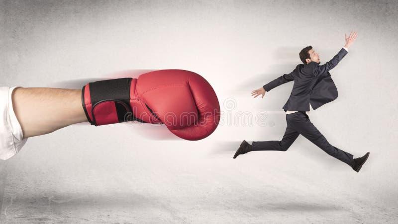 Бизнесмен получает увольнятьым огромной кладя в коробку рукой стоковое изображение