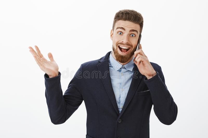 Бизнесмен получая превосходные новости Счастливый и excited услаженный симпатичный мужской предприниматель в элегантном удерживан стоковое фото rf