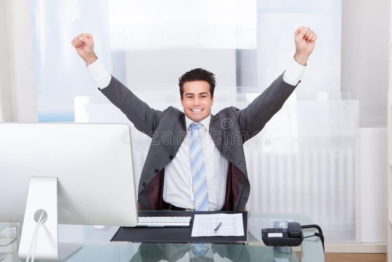 Бизнесмен поднимая его руки в утехе стоковая фотография