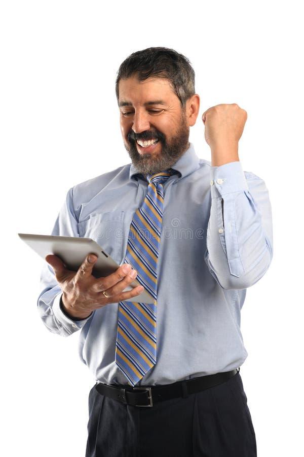 Бизнесмен празднуя пока смотрящ электронную таблетку стоковые изображения