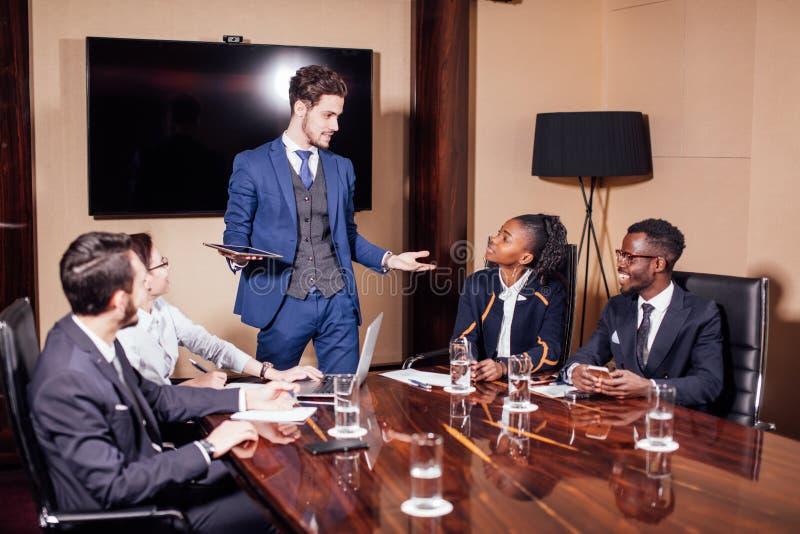 Бизнесмен представляя к коллегам на встрече стоковая фотография