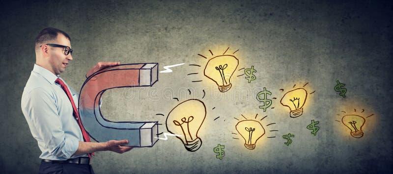 Бизнесмен привлекает электрические лампочки блестящих идей с большим магнитом стоковые изображения rf