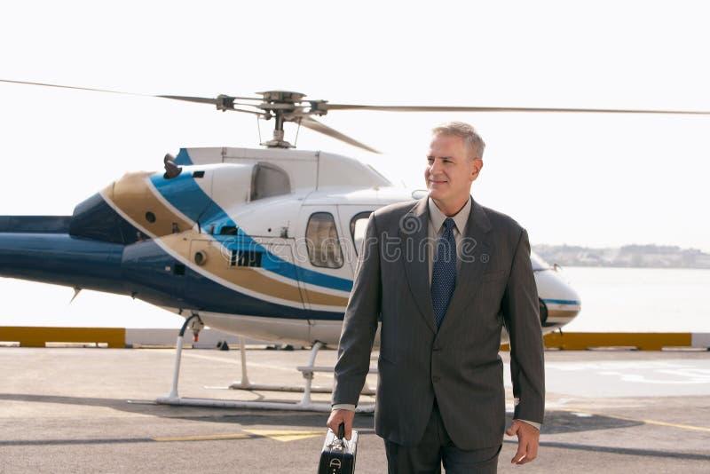 Бизнесмен приезжая на пусковую площадку вертолета стоковое изображение