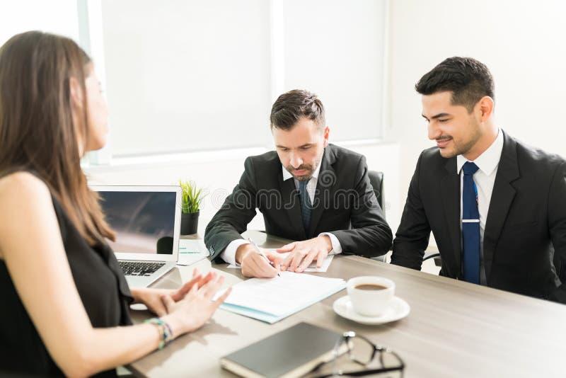 Бизнесмен признавая предложение и подписывая контракт стоковое изображение rf