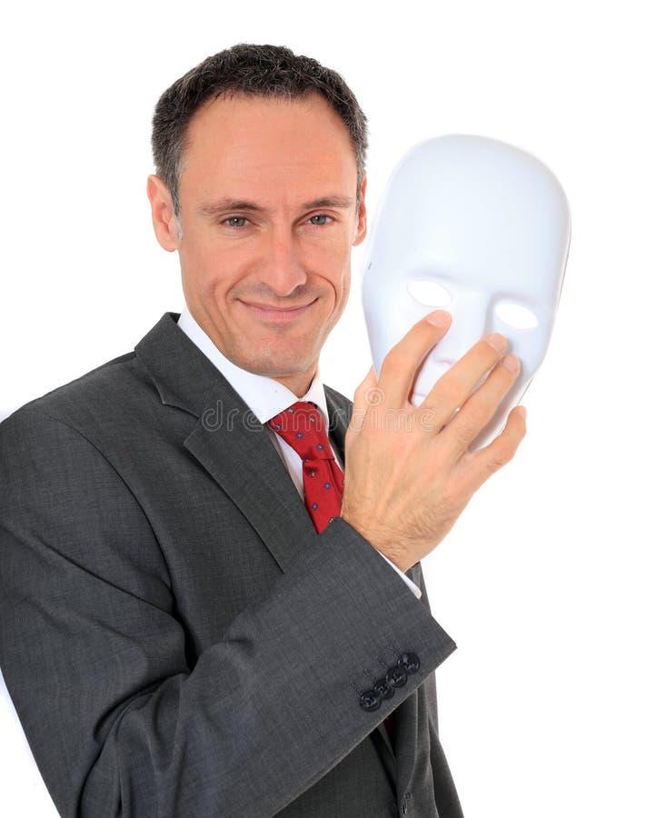 Бизнесмен принимает белую маску стоковое фото rf