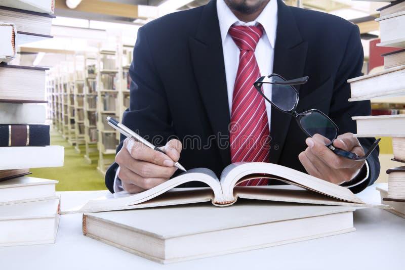 Бизнесмен принимая примечания на библиотеку стоковое изображение
