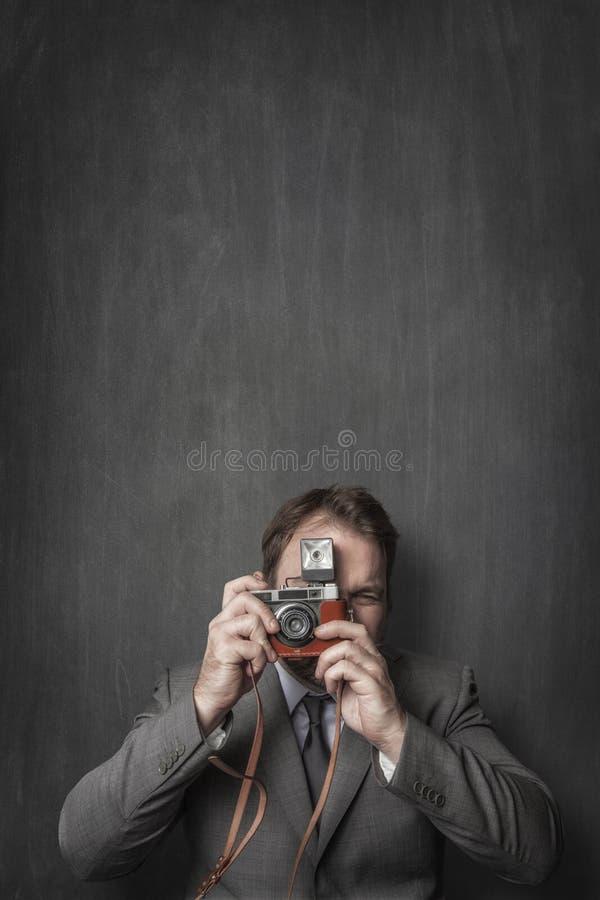 Бизнесмен принимая фото со старой винтажной камерой стоковое фото