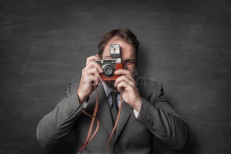 Бизнесмен принимая фото со старой винтажной камерой стоковая фотография rf