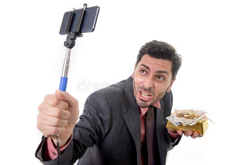Бизнесмен принимая фото selfie с представлять камеры и ручки мобильного телефона счастливый и успешный с баром и деньгами золота стоковые фотографии rf
