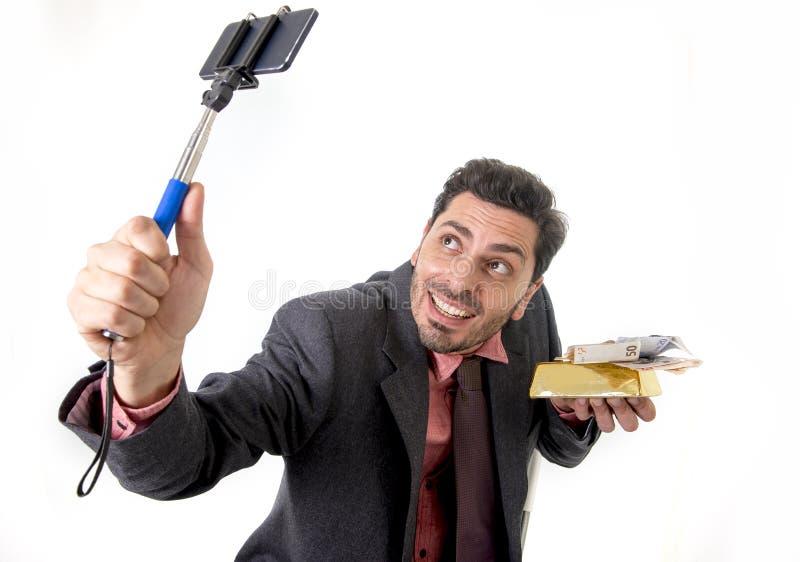 Бизнесмен принимая фото selfie с представлять камеры и ручки мобильного телефона счастливый и успешный с баром и деньгами золота стоковая фотография