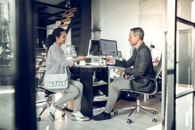 Бизнесмен принимая CV от молодой женщины перед собеседованием для приема на работу стоковое изображение