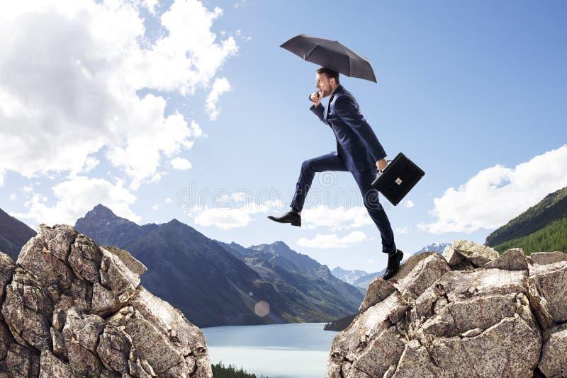 Бизнесмен при зонтик скача на горы стоковое фото rf