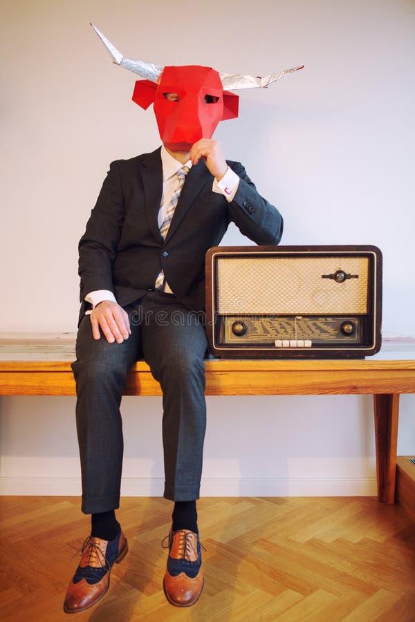 Бизнесмен при маска головы быка сидя рядом с винтажным радио стоковая фотография