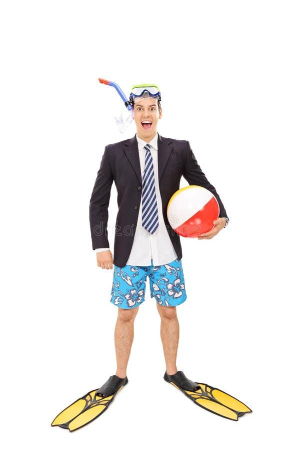 Бизнесмен при маска подныривания держа шарик пляжа стоковые изображения