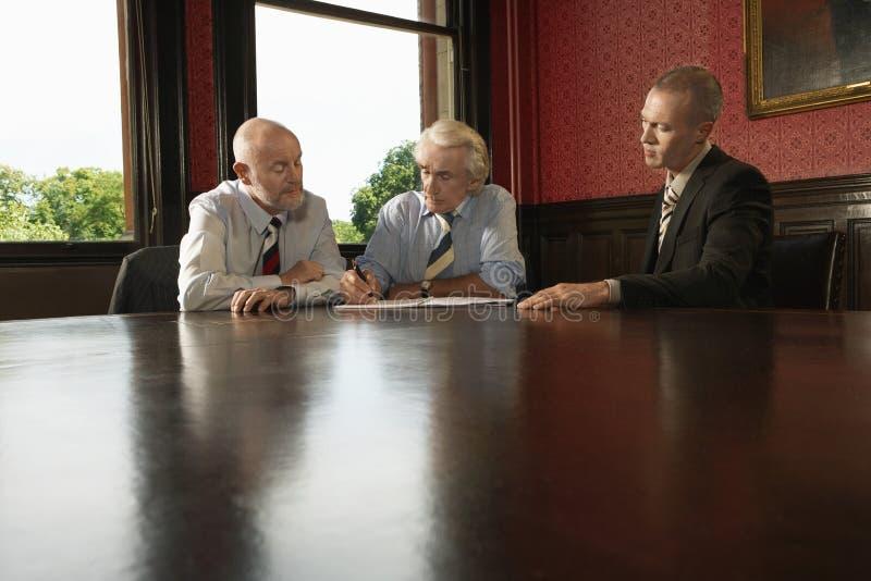 Бизнесмен при мужские коллеги подписывая контракт стоковая фотография