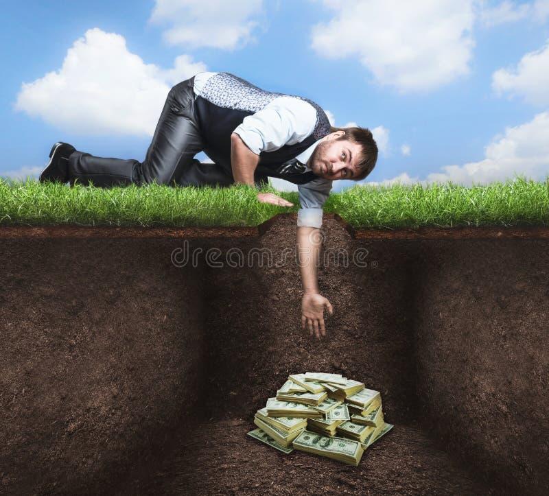 Бизнесмен пробуя получить сокровище в почве стоковая фотография rf
