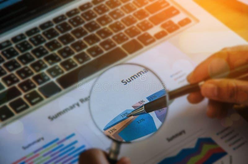 Бизнесмен проверяя диаграмму с лупой, крупным планом стоковое фото