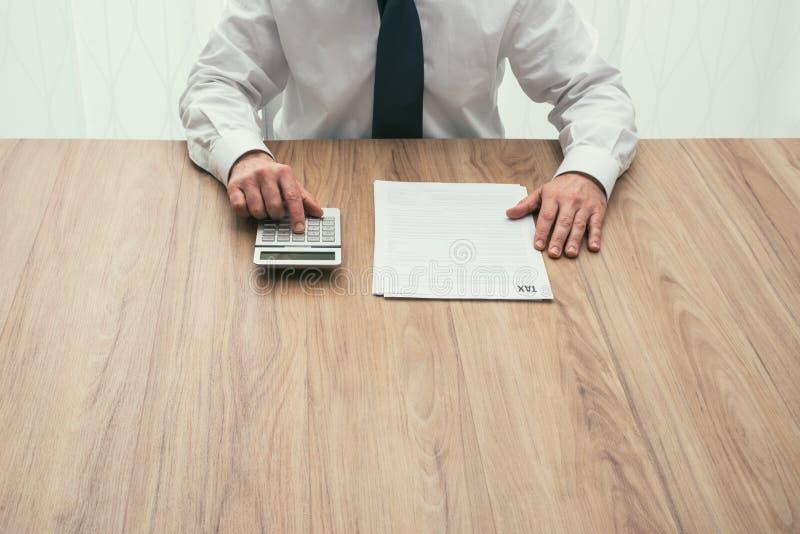 Бизнесмен проверяя налоговые формы стоковые фото