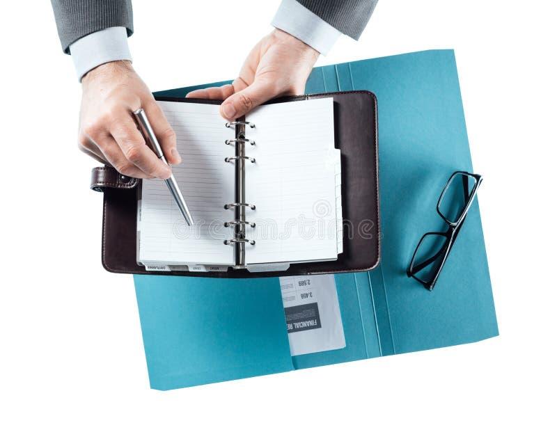 Бизнесмен проверяя план-график на организаторе стоковые изображения rf