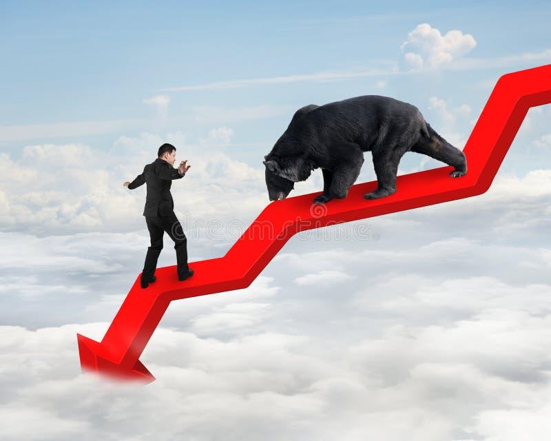 Бизнесмен против медведя на линии убывающего тренда стрелки с небом стоковые изображения rf